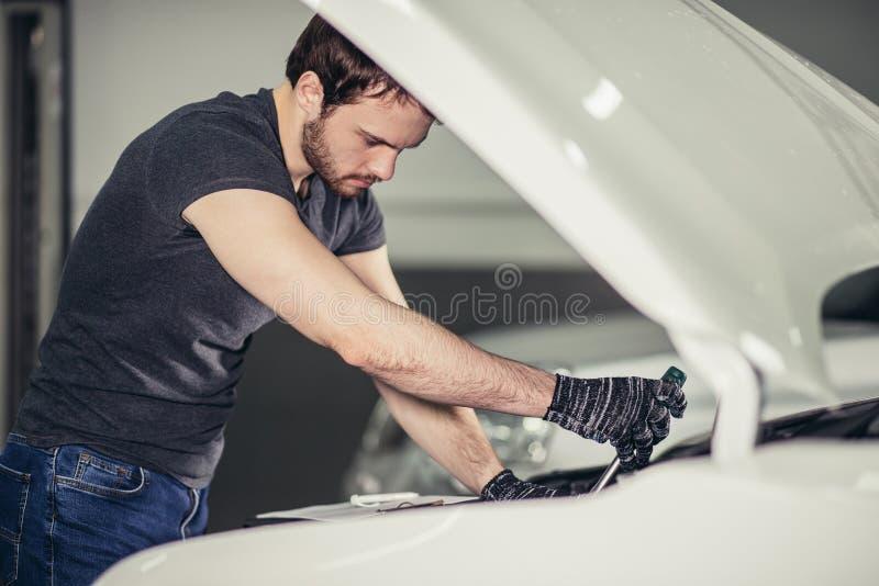 工作在修理车库的汽车敞篷下的技工 免版税库存照片