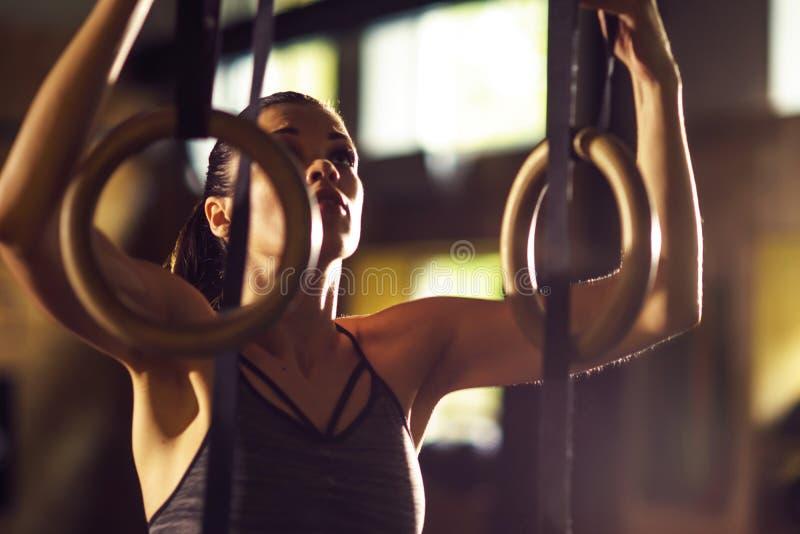 工作在健身房的适合,运动和运动女运动员 使用体操圆环的妇女训练 体育,竞技和 免版税库存照片