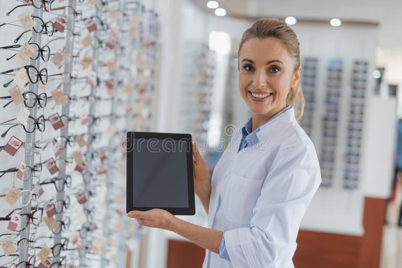 工作在光学的快乐的专业眼镜师 库存照片