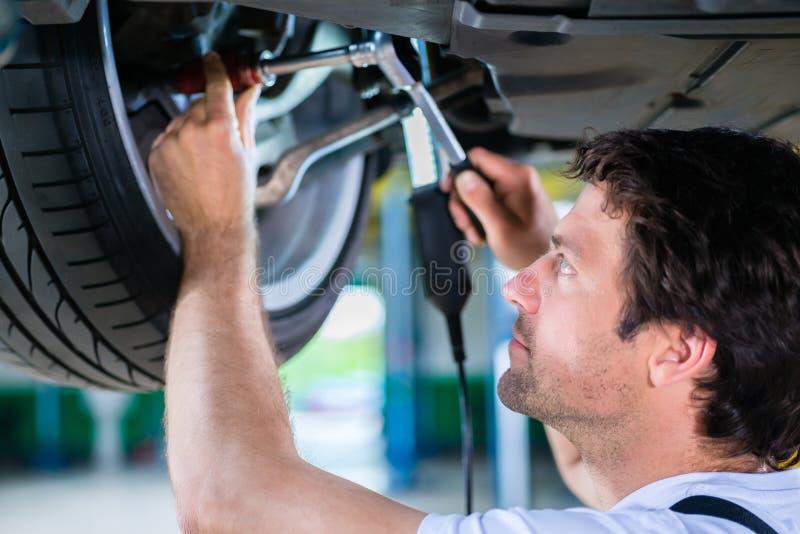 工作在关于轮子的汽车车间的技工 免版税库存照片