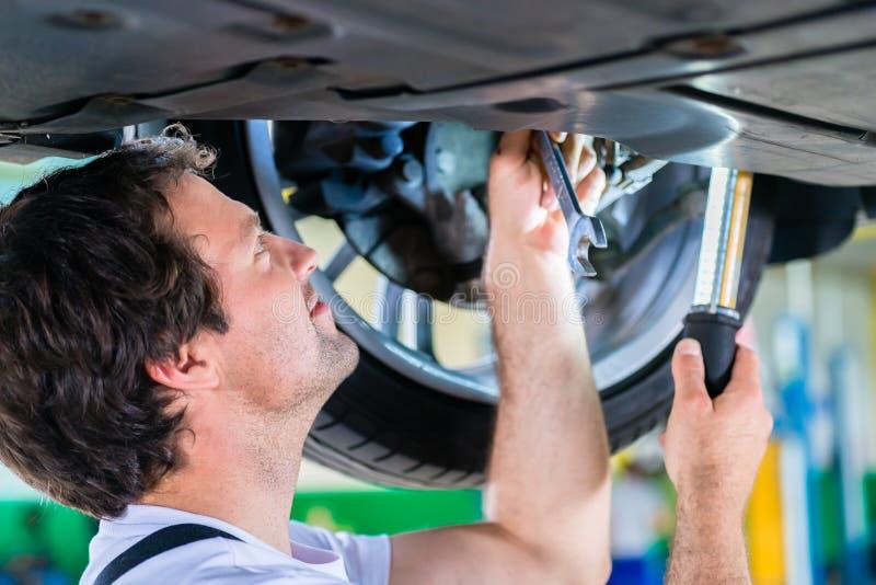 工作在关于轮子的汽车车间的技工 图库摄影