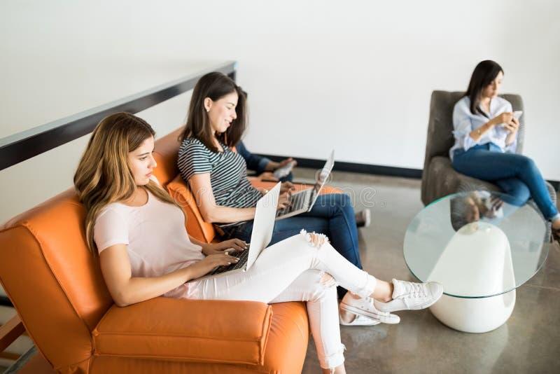 工作在办公室休息室的商人 免版税库存照片