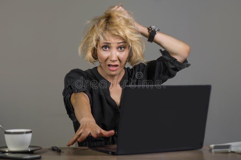 工作在办公室便携式计算机书桌感觉的年轻人被注重的和杂乱女商人生活方式画象疲倦和被淹没 库存图片