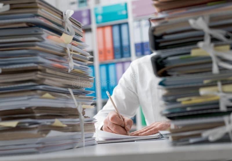 工作在办公室和堆的商人文书工作 库存照片