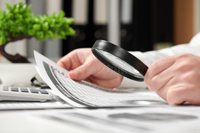 工作在办公室和计算财务的商人 扩大化的玻璃使用 企业财务会计概念 免版税库存图片
