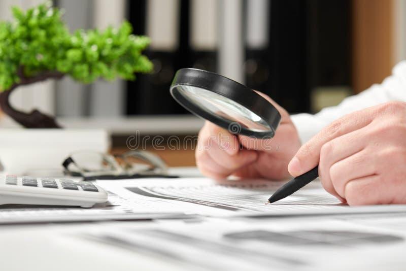 工作在办公室和计算财务的商人 扩大化的玻璃使用 企业财务会计概念 库存图片