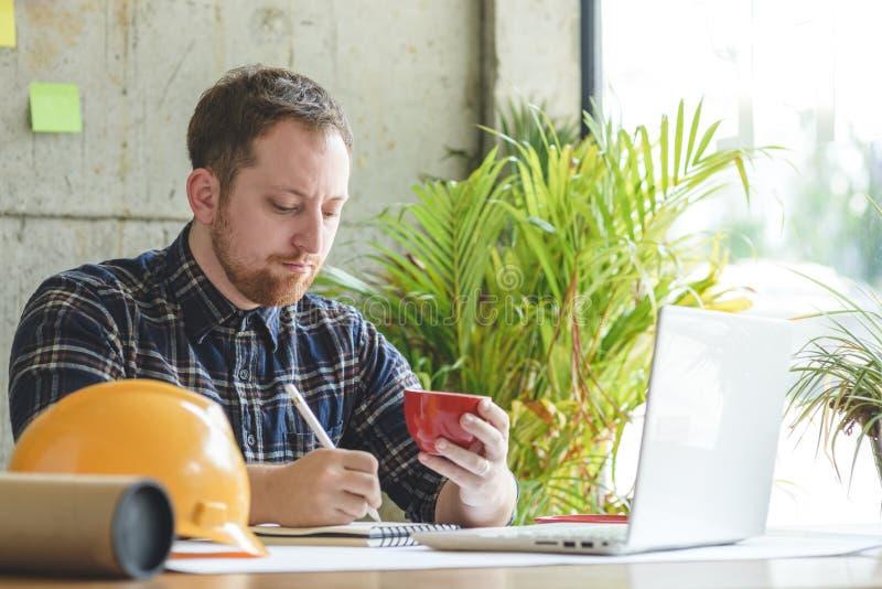 工作在办公室和饮用的咖啡的工程师 免版税库存图片