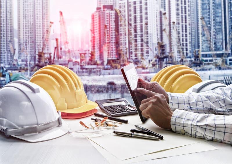 工作在办公室桌上的承包商人反对工地工作项目 免版税库存图片