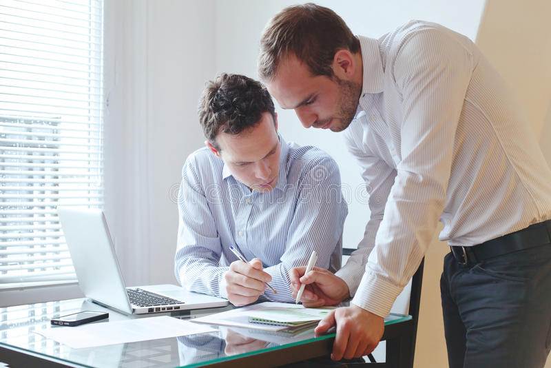 工作在办公室的两个商人 免版税图库摄影