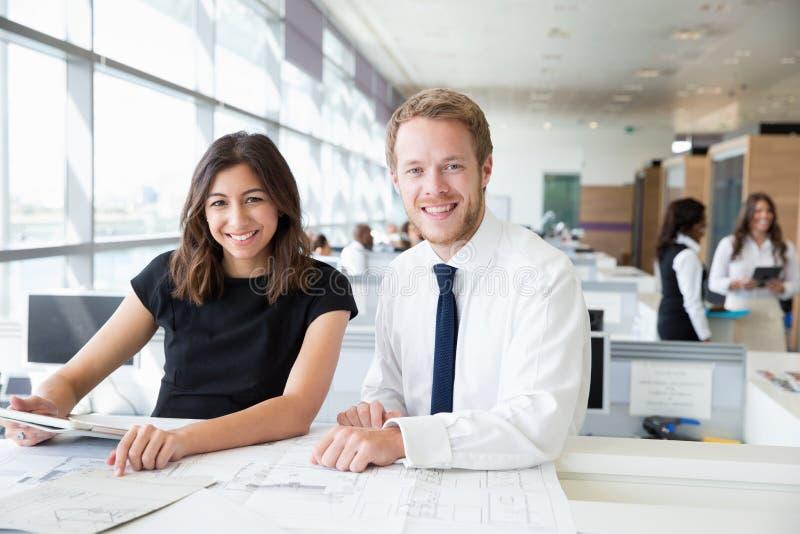 工作在办公室的两位年轻建筑师,微笑对照相机 免版税图库摄影