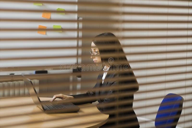 工作在办公室的严肃的女实业家 免版税库存图片