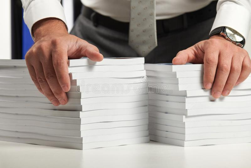 工作在办公室的商人,读堆书和报告 r 免版税图库摄影