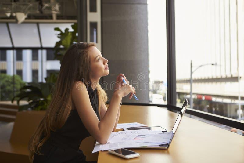 工作在办公室的女实业家看在窗口外面 免版税库存图片