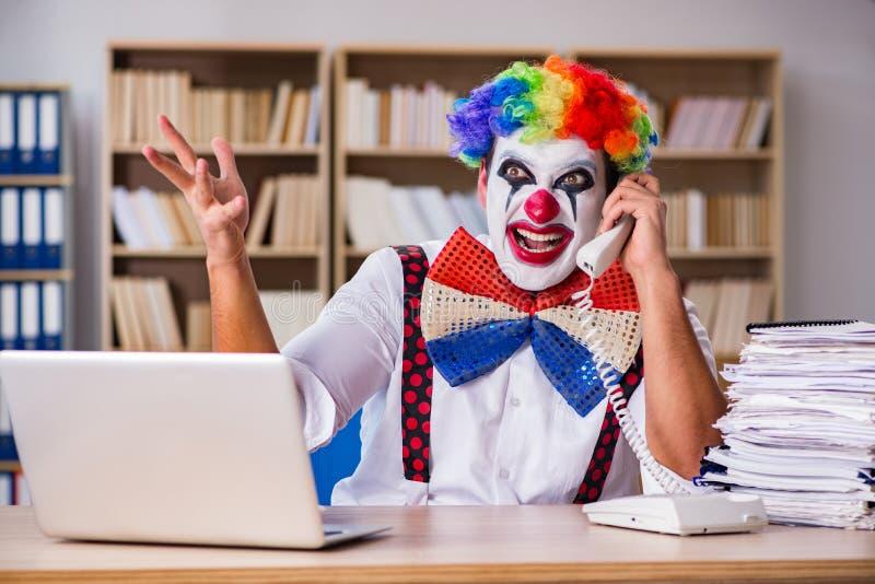工作在办公室的小丑商人 免版税库存照片