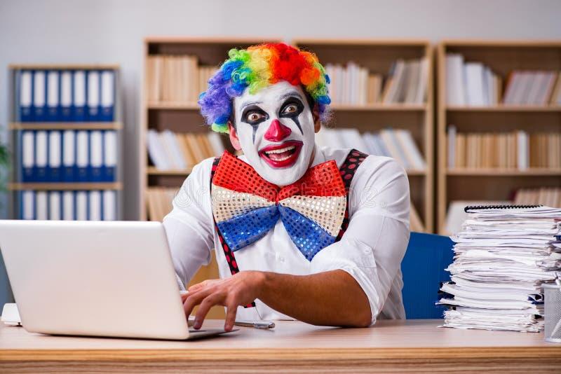 工作在办公室的小丑商人 图库摄影