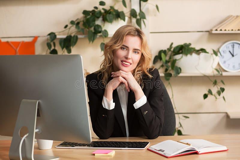 工作在办公室的少妇,坐在书桌 免版税库存照片