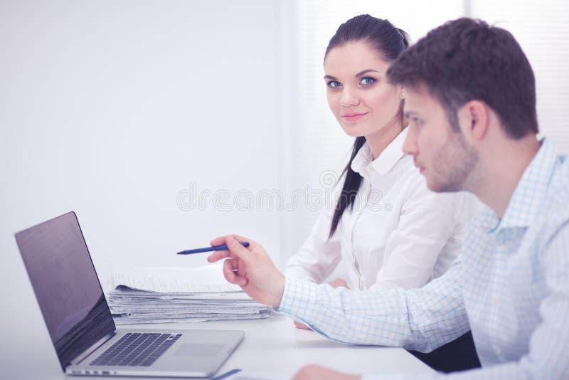 工作在办公室的年轻商人,坐在书桌,看手提电脑屏幕 免版税库存照片