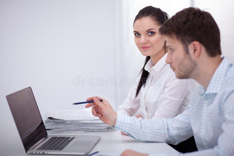 工作在办公室的年轻商人,坐在书桌,看手提电脑屏幕 免版税库存图片
