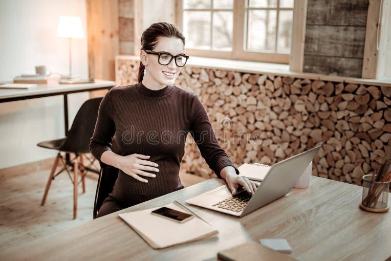 工作在办公室的快乐的好妇女 免版税图库摄影