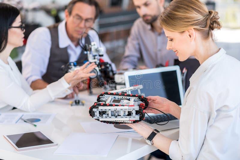 工作在办公室的快乐的被集中的小组科学家 图库摄影