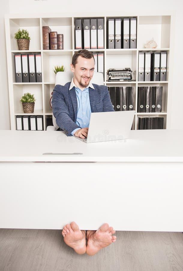 工作在办公室的愉快的赤足商人 免版税库存图片