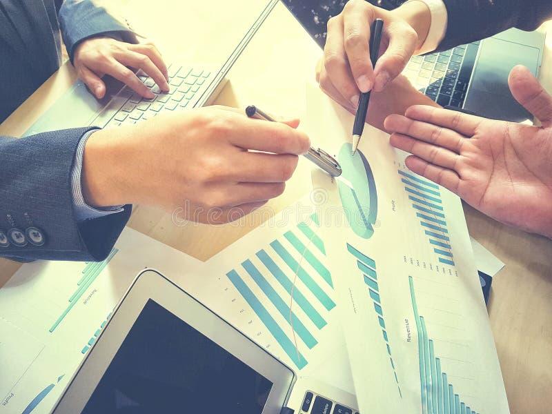 工作在办公室的成功的集团谈话和当前与图表为描述和谈论公司的赢利 免版税库存照片