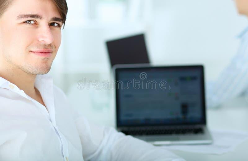 工作在办公室的新生意人,坐在服务台 免版税库存图片