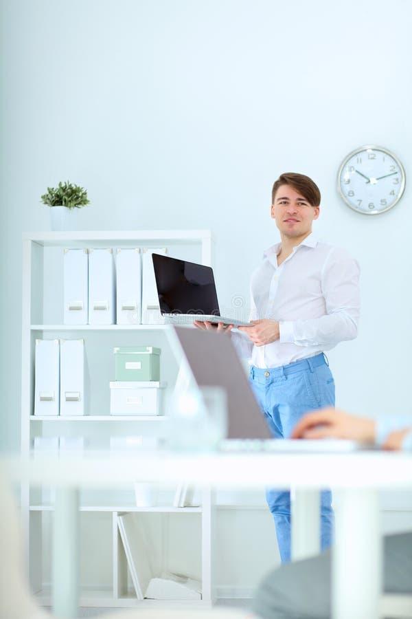 工作在办公室的新生意人,坐在服务台 图库摄影