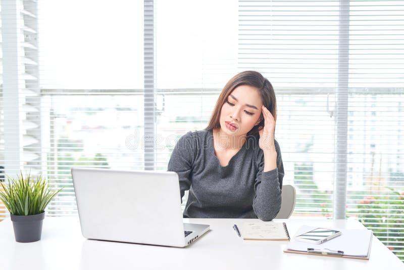 工作在办公室的美丽的年轻亚裔女商人使用手提电脑 库存照片