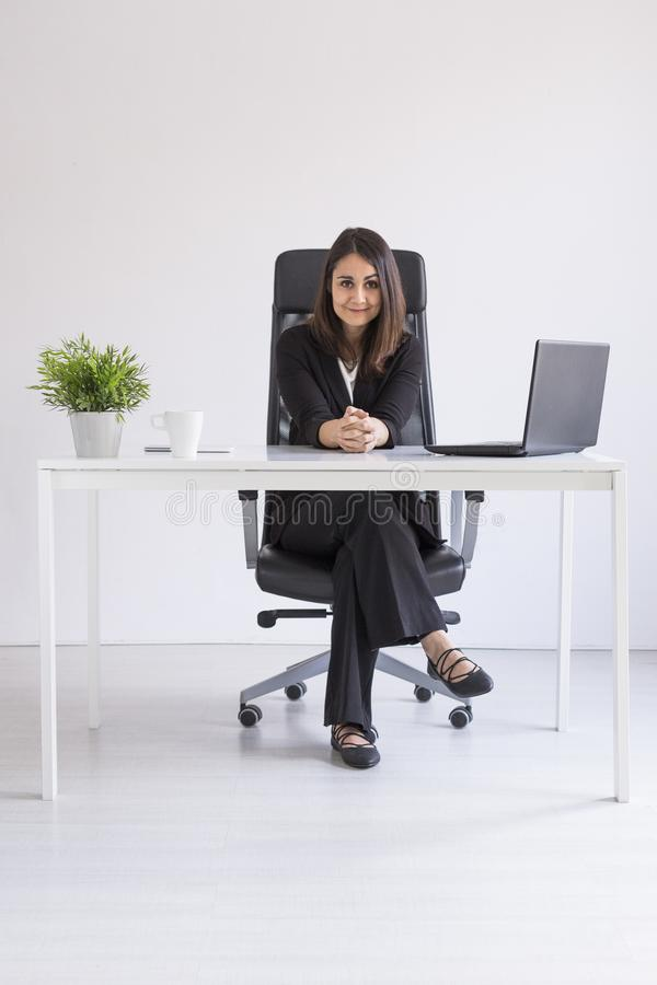 工作在办公室的美丽的年轻女商人,使用她的膝上型计算机 到达天空的企业概念金黄回归键所有权 白色背景 户内 库存照片