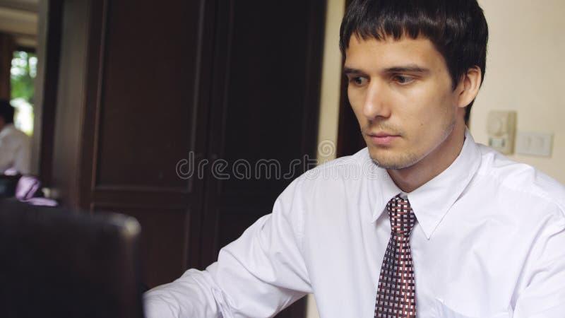 工作在办公室的英俊的严肃的年轻商人 键入在膝上型计算机的年轻人 库存图片