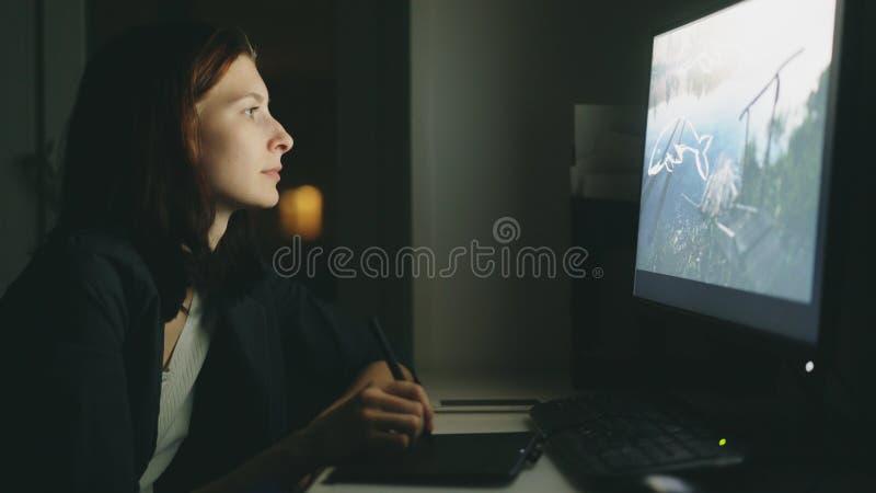 工作在办公室的被集中的少妇设计师在晚上使用计算机和图形输入板完成工作 免版税库存图片