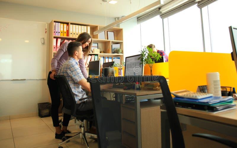 工作在办公室的队 监测键入和新项目谈论 免版税库存图片