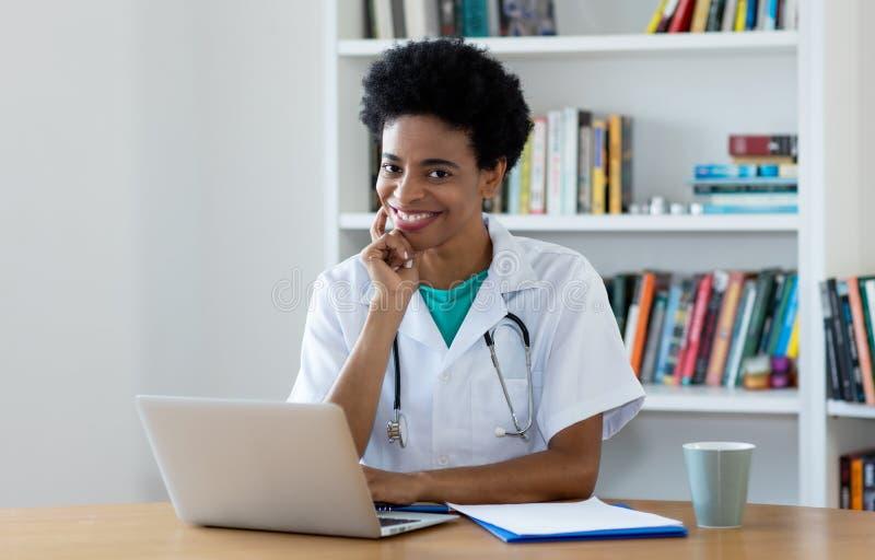 工作在办公室的非裔美国人的成熟女性医生 图库摄影
