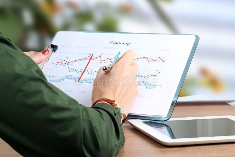 工作在办公室的年轻女实业家,坐在她的书桌,分析在图表的数据,指向由笔 免版税图库摄影