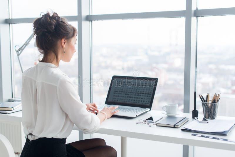 工作在办公室的年轻女实业家,键入,使用计算机 搜寻信息的被集中的妇女网上,后方 库存照片