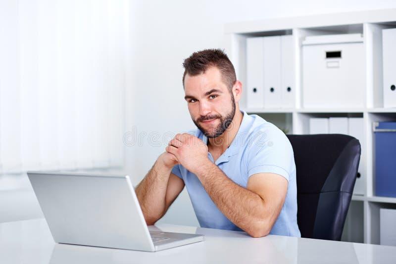 工作在办公室的年轻英俊的商人 免版税库存照片