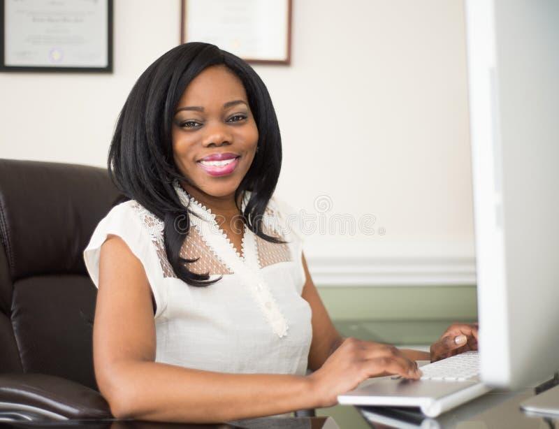工作在办公室的年轻非裔美国人的妇女 免版税库存照片