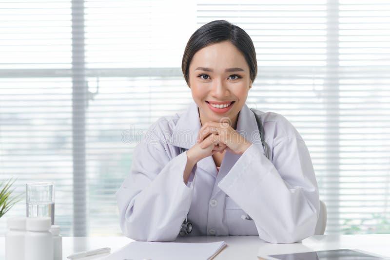 工作在办公桌和微笑的女性医生 库存照片