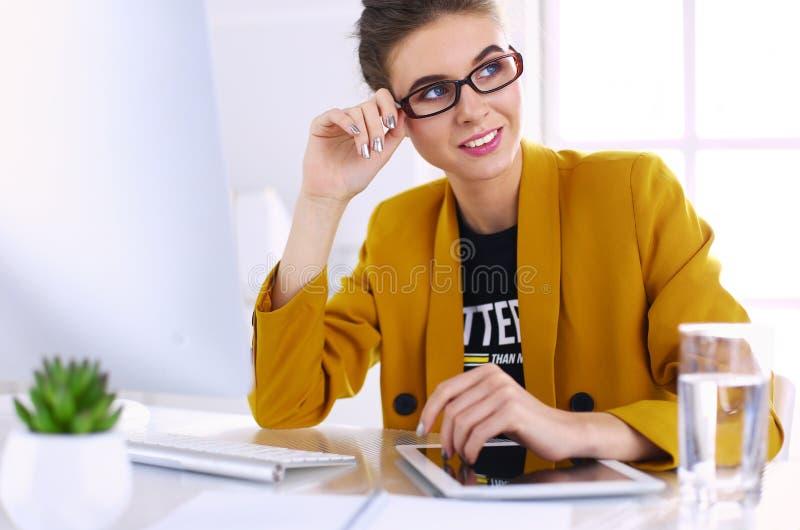 工作在办公桌和键入与膝上型计算机的年轻确信的女实业家 免版税库存照片