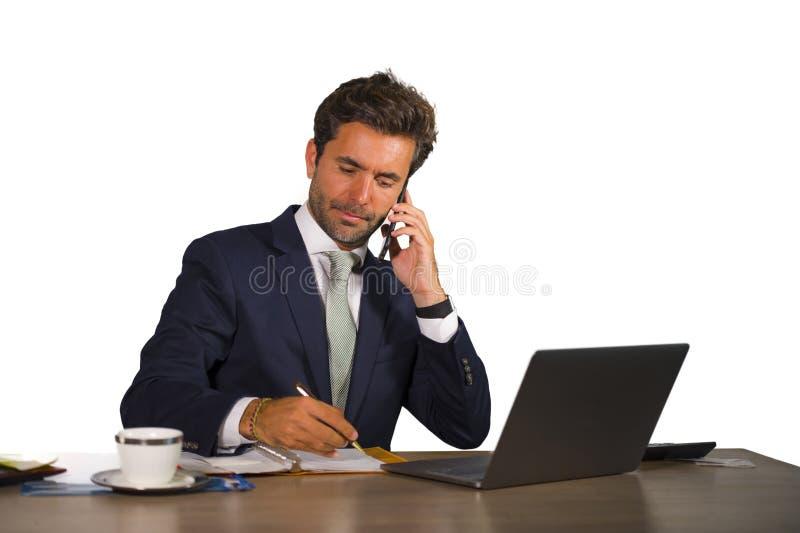 工作在办公桌的年轻英俊和可爱的商人公司公司被隔绝的画象谈话在手机co 免版税库存照片