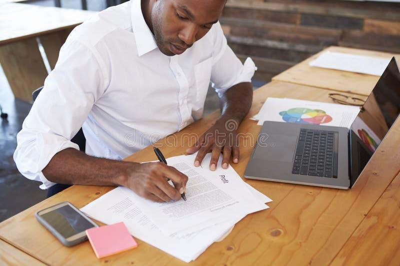 工作在办公桌的高的观点的年轻黑人 库存图片