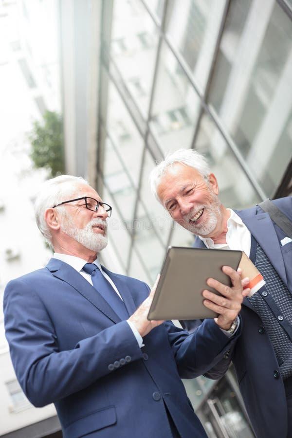 工作在办公楼前面的一个片剂身分的两个微笑的资深商人 免版税库存照片