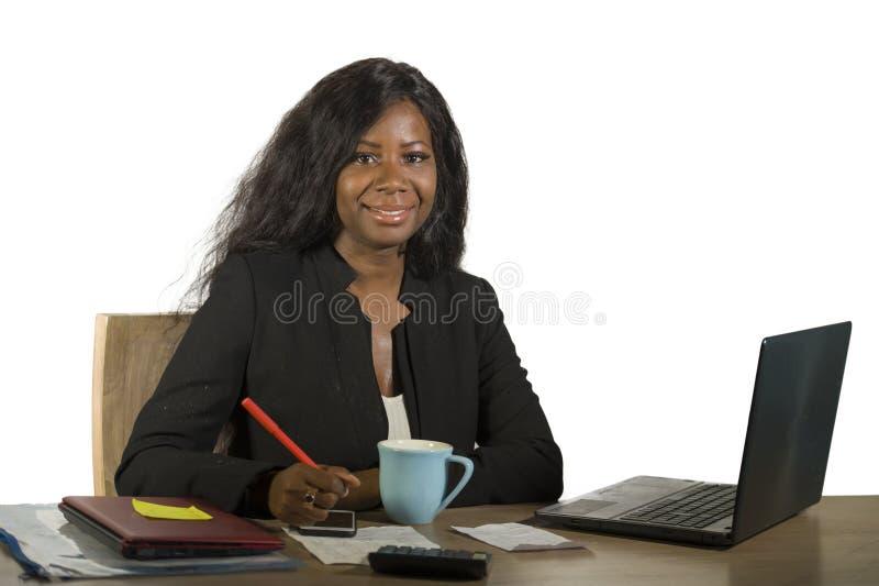 工作在办公计算机书桌微笑的成功摆在的年轻愉快和可爱的黑人美国黑人的女商人公司 免版税库存图片