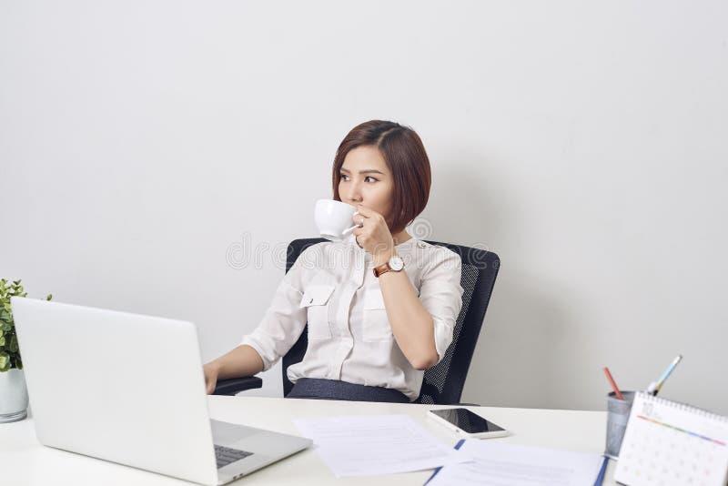 工作在办公计算机书桌微笑的饮用的咖啡的年轻愉快和可爱的亚裔女商人轻松和 库存图片
