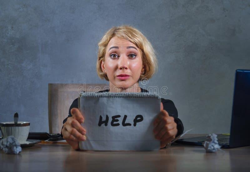 工作在办公计算机书桌的年轻美丽的哀伤和被注重的女商人拿着笔记薄请求感到的帮忙绝望 免版税库存照片