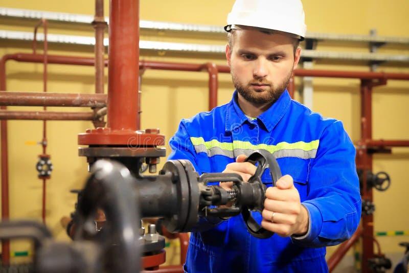 工作在加热的驻地的现代工业机器操作员 工作者转动管道闸式阀  工作服的人关闭阀门 免版税图库摄影