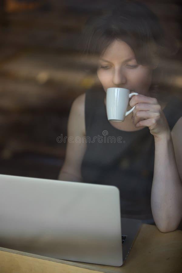 工作在午餐期间的严肃的妇女 免版税图库摄影