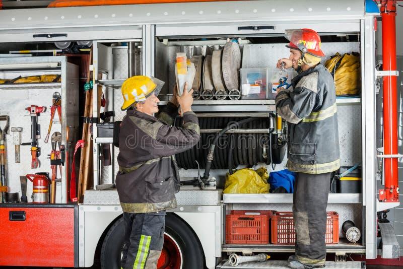 工作在卡车的微笑的消防队员 免版税库存照片