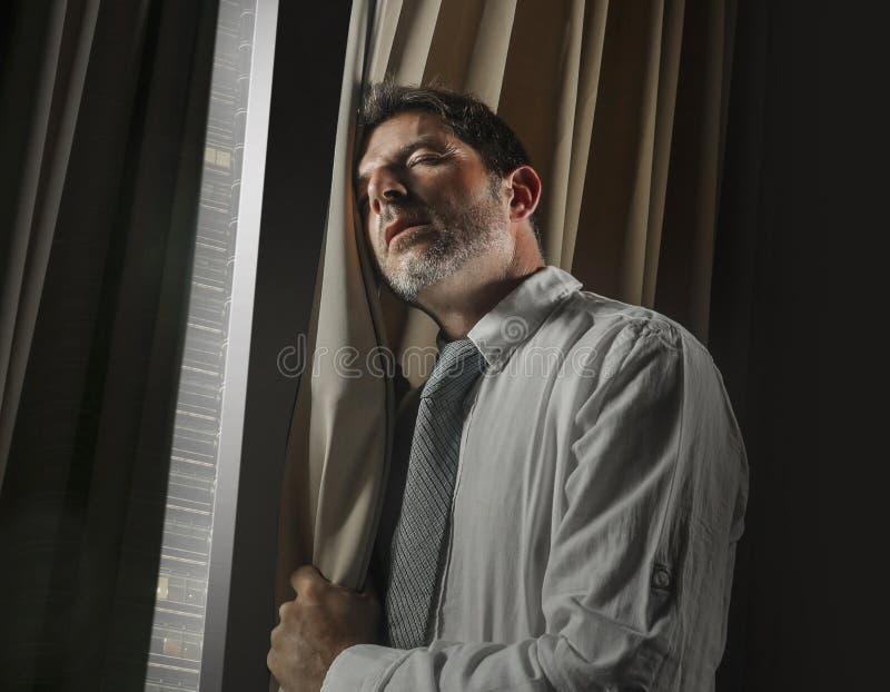 工作在压力下感觉的年轻被注重的和被淹没的商人夜间办公室画象沮丧和担心 免版税库存照片